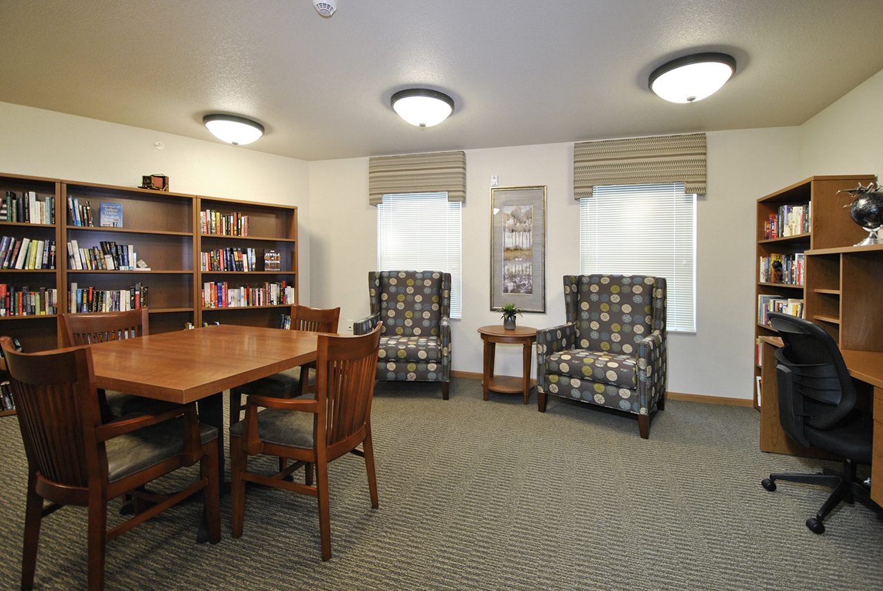 Study seating area and bookshelves at Grandhaven Manor